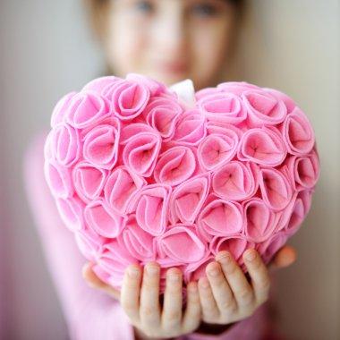 Pretty toddelr girl holding pink heart pendant