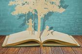 Fotografia taglio di carta dei bambini leggere un libro e bambini sullaltalena sotto tr
