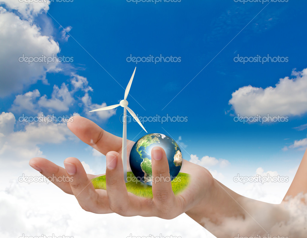 Wind turbines and earth on hand over blue sky