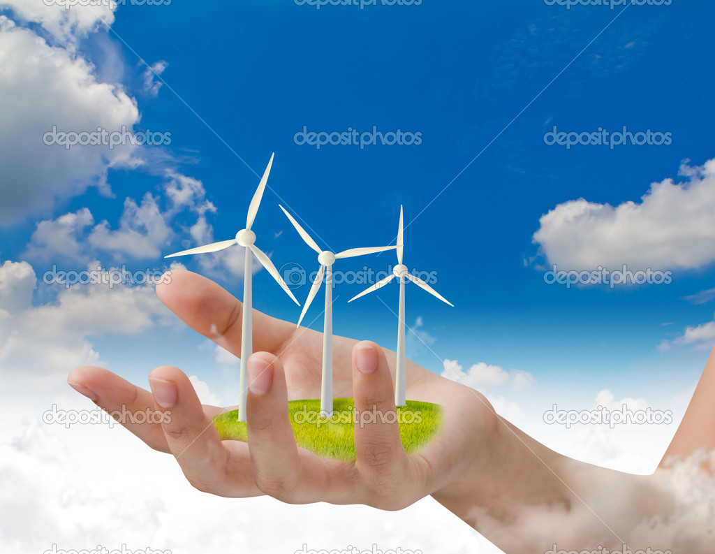 Wind turbines on hand over blue sky