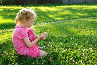 Young girl in pink picking up flowers in a field