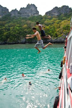 Travellers leap from the deck into the water.