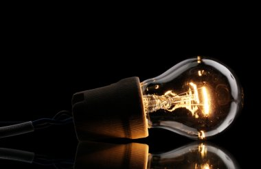 A lit light bulb on black background