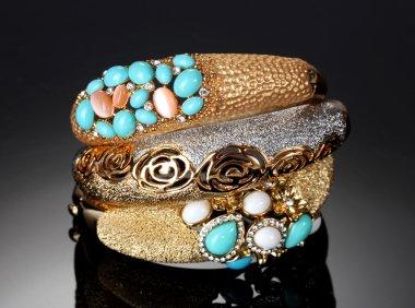 Beautiful golden bracelets on grey background