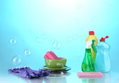 Washing dishes. Cleaning products on bright blue background