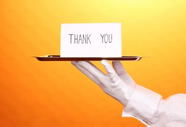Hand in glove holding silver tray with card saying thank you on yellow background