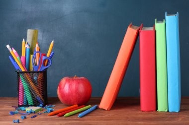 Composition of books, stationery and an apple on the teachers desk in the background of the blackboard