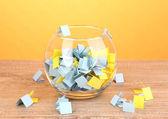 kousky papíru pro loterie v váza na dřevěný stůl na žlutém podkladu