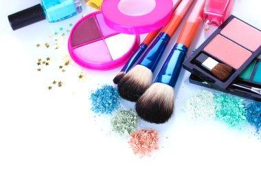 Eye shadow, nail polish and make-up brushes isolated on white