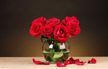 Beautiful red roses in vase on wooden table on brown background