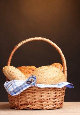 Delicious bread in basket on wooden table on brown background