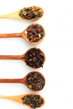 Different kinds of green and black dry tea in woooden spoon isolated on whi