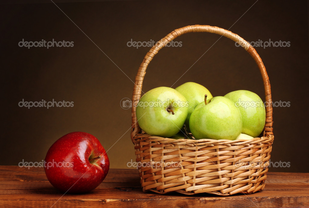 green and red apples in basket. juicy green apples in basket and red apple on wooden table brown backgro \u2014 stock