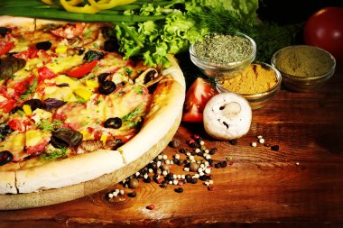 Delicious pizza, vegetables and spices on wooden table