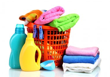 Clothes with detergent and washing powder in orange plastic basket isolated