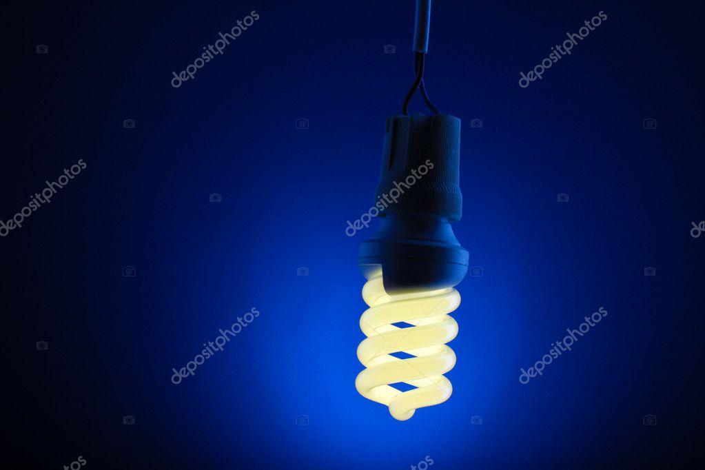 Un Acceso Lampadina Risparmio Energetico Luce Su Sfondo Blu Foto