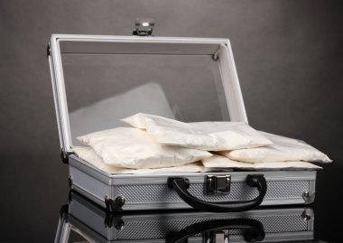 Сocaine in a suitcase on grey background
