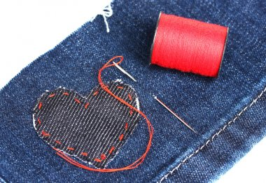 Heart-shaped patch on jeans wiht needle and thread closeup