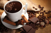 Photo Cup of hot chocolate, cinnamon sticks, nuts and chocolate on wooden table