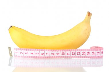 Ripe banana and measuring tape isolated on white