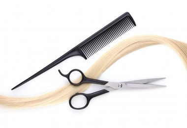 Shiny blond hair with hair cutting shears and comb isolated on white