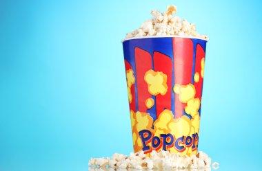 Full bucket of popcorn on blue