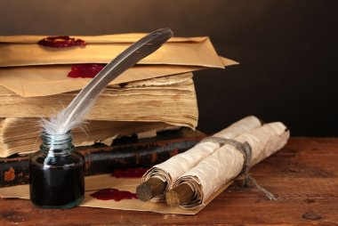 Old books, scrolls, feather pen and inkwell on wooden table on brown background