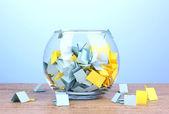 kousky papíru pro loterie v váza na dřevěný stůl na modrém pozadí