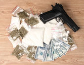 Fotografie Cocaine and marihuana in packages, dollars and handgun on wooden background