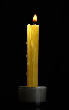 Yellow candle on black background