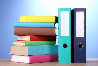 Bright office folders and books on wooden table on blue background