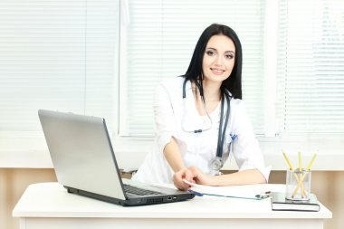 Beautiful girl doctor in the office holding prescription