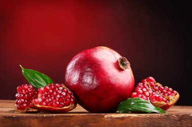 Ripe pomegranate fruit with leaves on wooden table on red background
