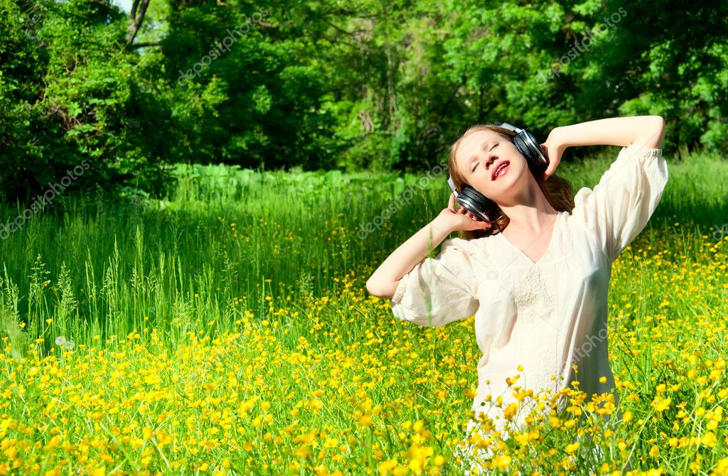 Beautiful girl in headphones enjoying the music in a field of fl