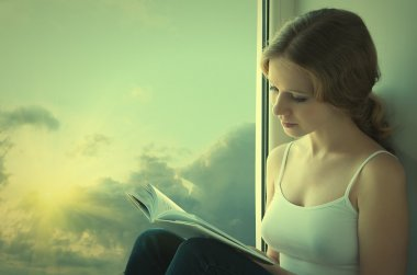 Beautiful young woman reading a book while sitting at a window i