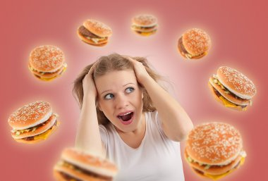 Diet concept. young woman is under stress, burgers are flying ar