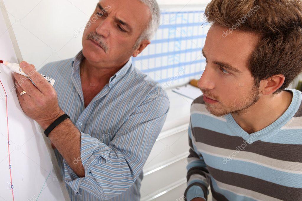 Учитель и ученик, глядя на график на доске — Стоковое фото ...