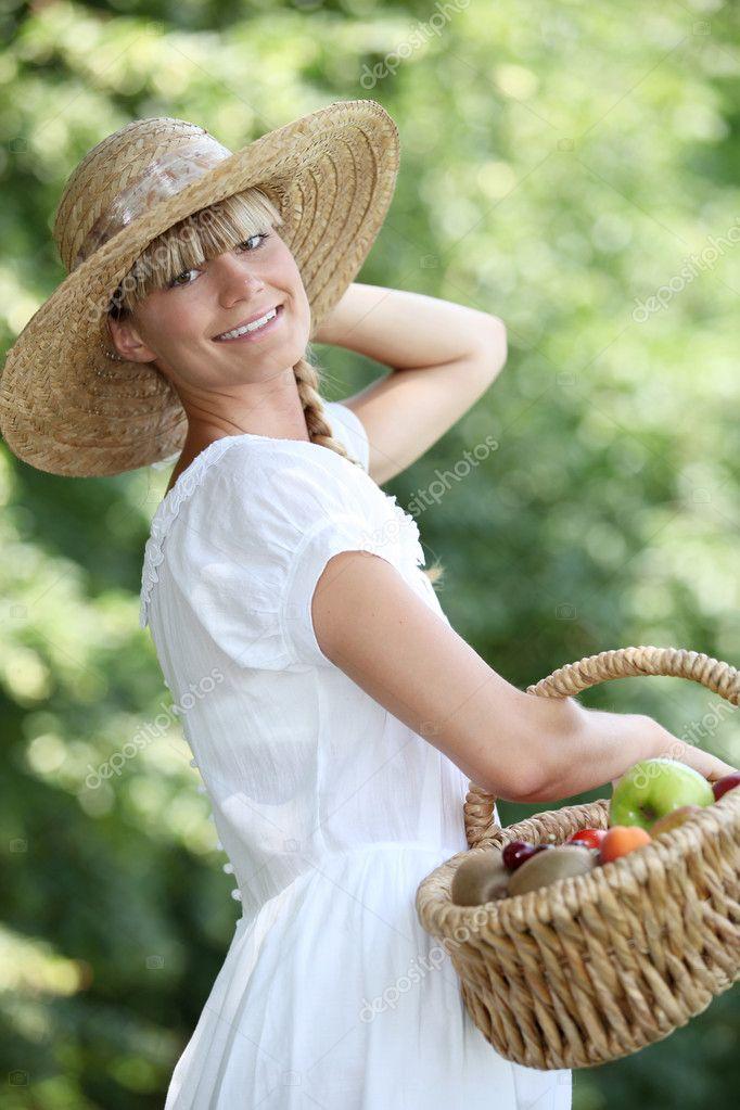 Mulher despreocupada com uma palha chapéu e vime cesta cheia de frutas —  Fotografia de Stock 02b301d9d02