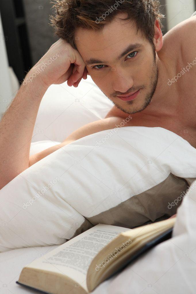 Jeune homme lisant un livre dans son lit photographie - Comment attirer un homme dans son lit ...