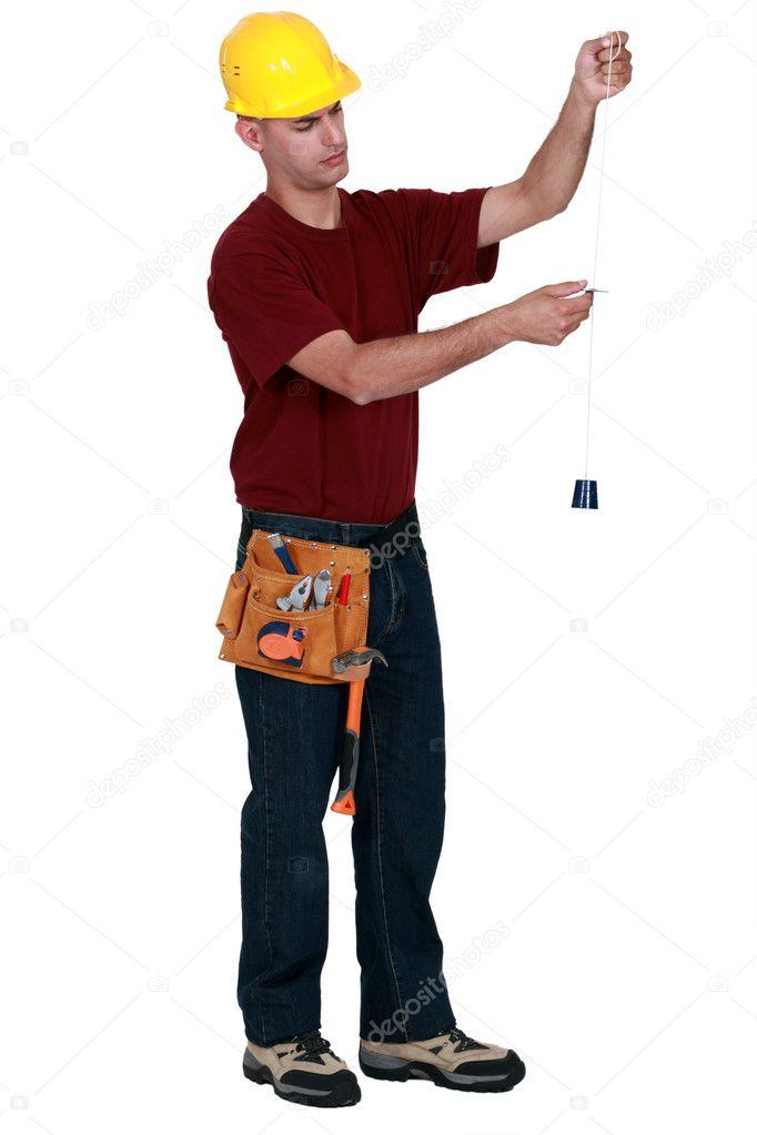 Artigiano in possesso di uno strumento di misura della for Piani di gabinetto artigiano