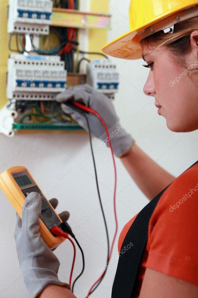 weibliche Elektriker überprüft die Verdrahtung auf einem ...