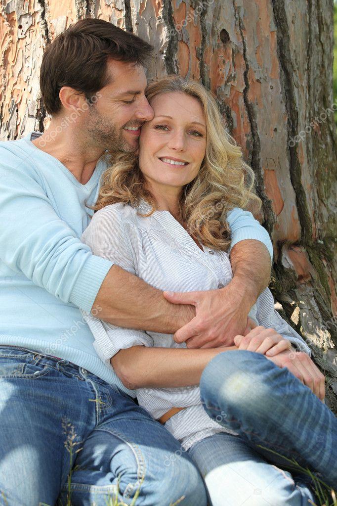 Paar kuschelt vor einem Baum — Stockfoto © photography33