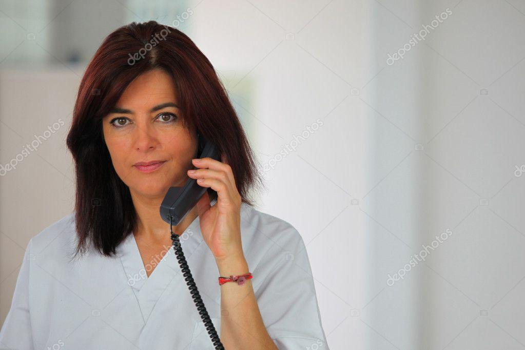 Женщина сделать звонок на стационарный телефон — стоковое фото.