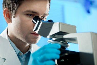 Scientist looks into microscope
