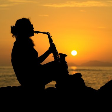 Woman Playing the Saxophone at Sunset