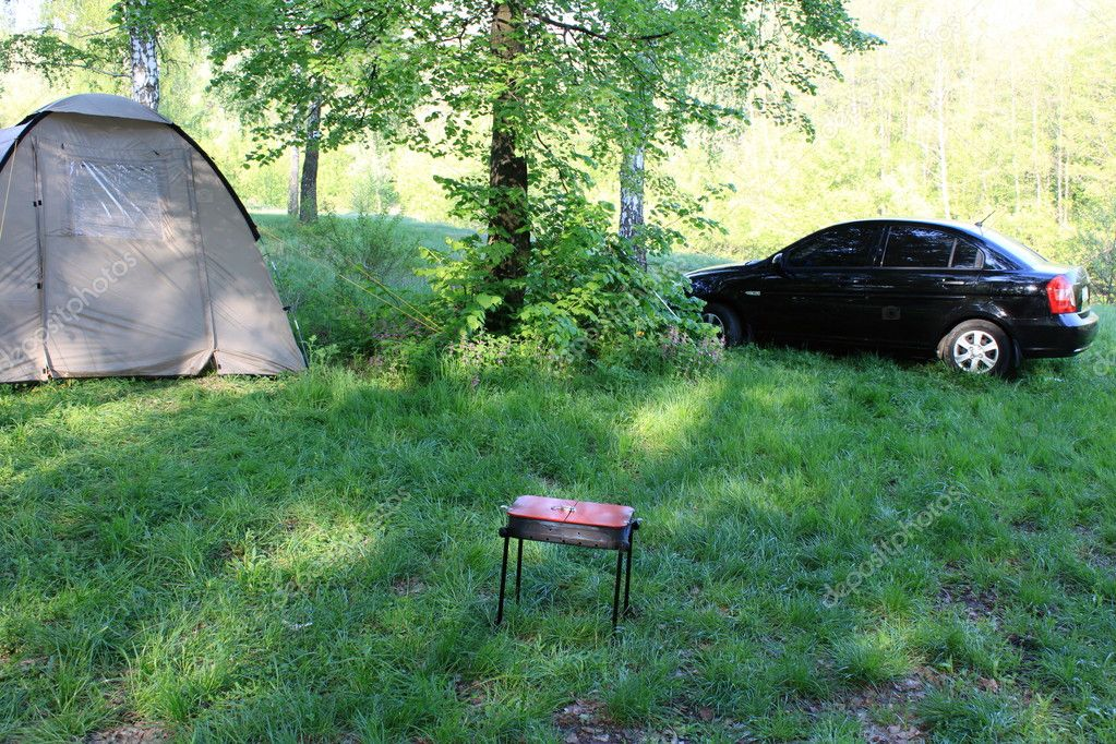 A tent, a car and a barbecue in the summer