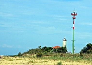 New and old lighthouse beacon on a sandy beach