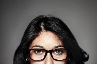 Appearing woman with glasses on gray background