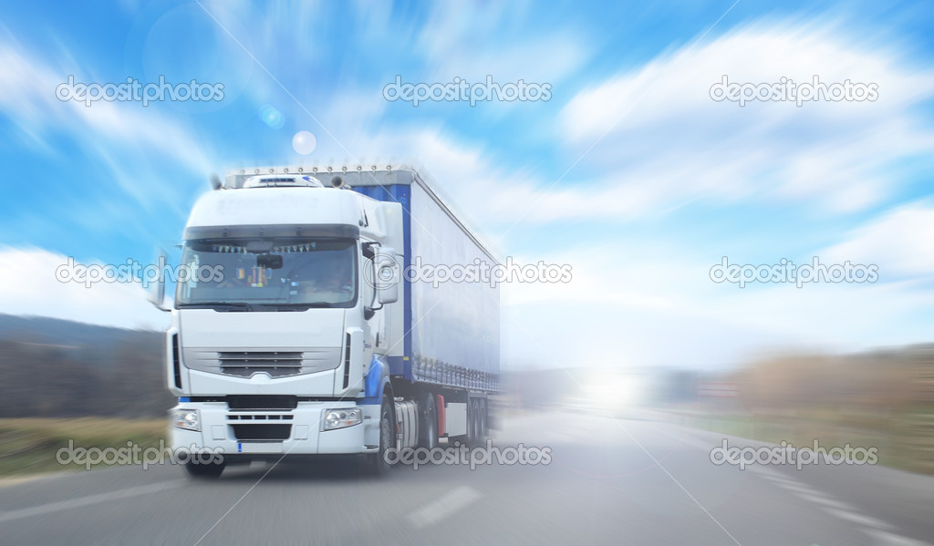 Truck on blurry road over blue cloudy sky background