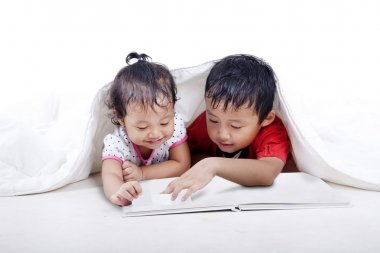 Sibling reading book under the balnket